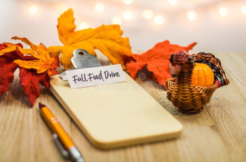 Concetto della lista dell'azionamento dell'alimento di caduta sulla lavagna per appunti in bianco circondata con le foglie lumino fotografie stock