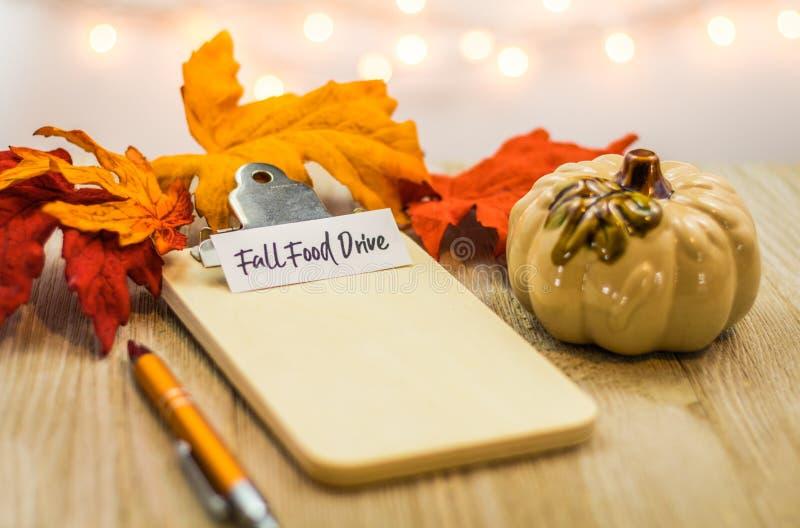 Concetto della lista dell'azionamento dell'alimento di caduta sulla lavagna per appunti in bianco circondata con le foglie lumino fotografie stock libere da diritti