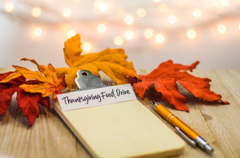 Concetto della lista dell'azionamento dell'alimento di ringraziamento sulla lavagna per appunti in bianco circondata con le fogli immagini stock