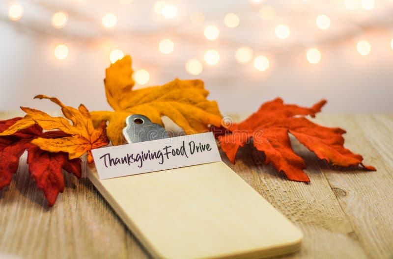Concetto della lista dell'azionamento dell'alimento di ringraziamento sulla lavagna per appunti in bianco circondata con le fogli immagine stock