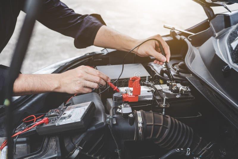 Concetto della macchina del motore di automobile di servizi, mani del riparatore del meccanico di automobile che controllano un'o fotografia stock