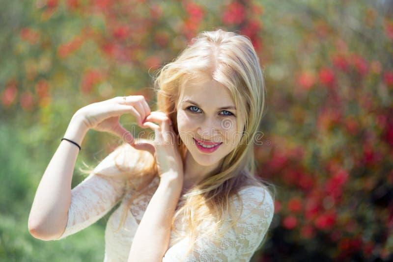 Concetto della natura di amore di gesto - giovane donna bionda sorridente che mostra forma del cuore fatta delle dita durante la  fotografia stock
