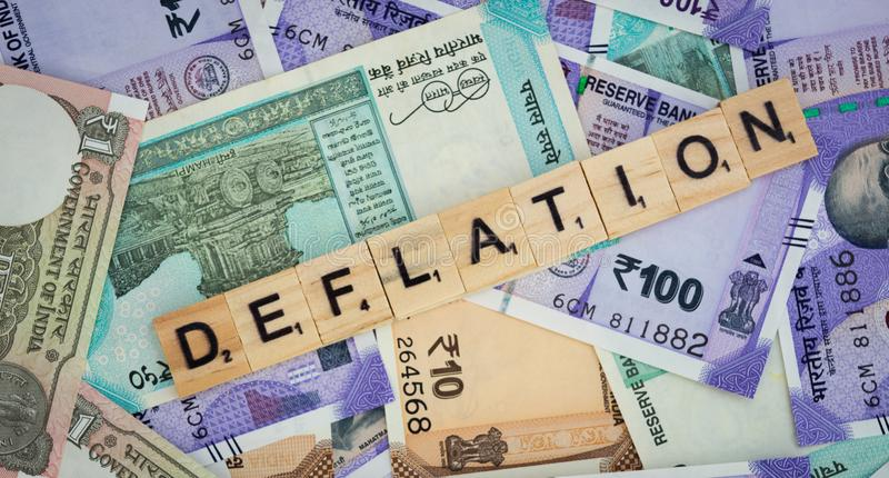 Concetto della parola di deflazione sulle note indiane di valuta immagine stock libera da diritti