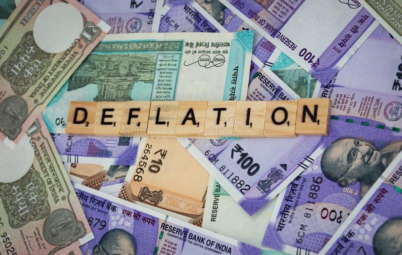Concetto della parola di deflazione sulle note indiane di valuta immagine stock