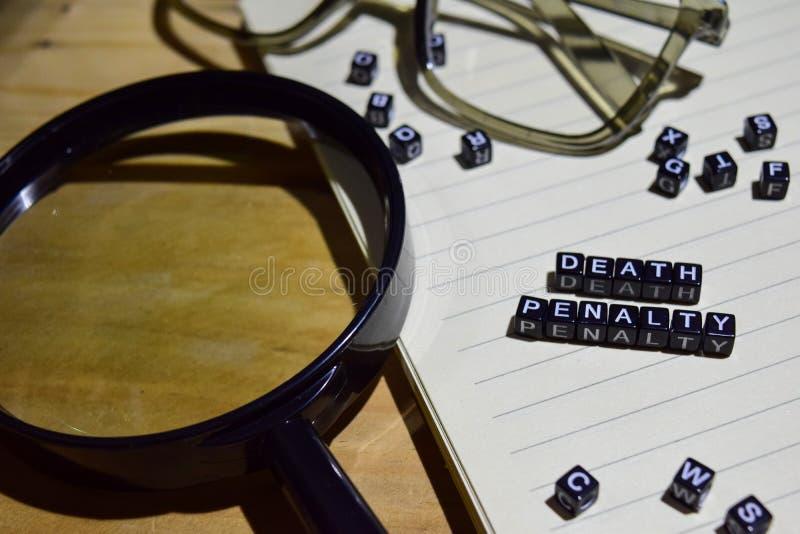 Concetto della pena di morte sui cubi di legno con la lente d'ingrandimento, occhio di vetro, libri nel fondo d'annata fotografia stock