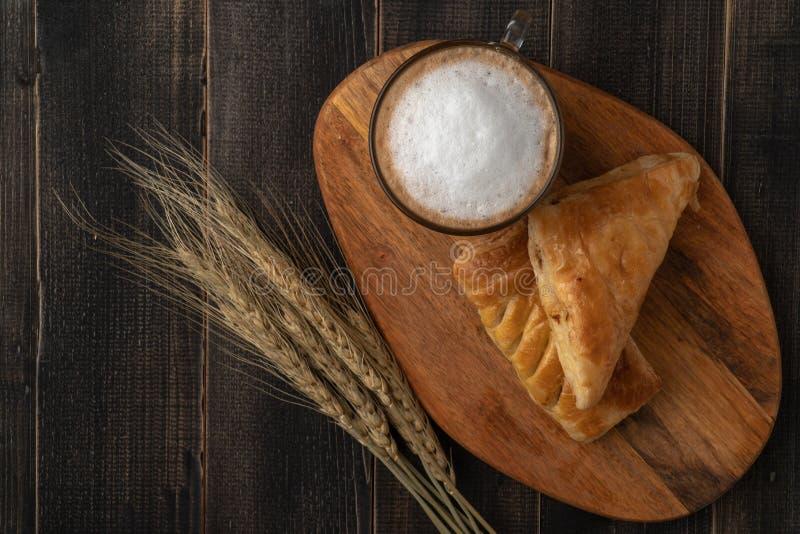 Concetto della prima colazione perfetta di mattina Tazza e croissant bianchi del caffè per la prima colazione su fondo di legno s immagini stock libere da diritti