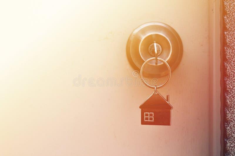 Concetto della proprietà, chiave domestica con il keychain della casa del metallo in buco della serratura fotografia stock libera da diritti