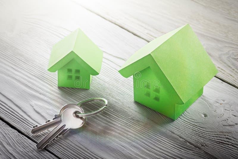 Concetto della proprietà, chiave e casa di carta con le finestre di schizzo su fondo di legno leggero Idea per il concetto del be immagini stock libere da diritti