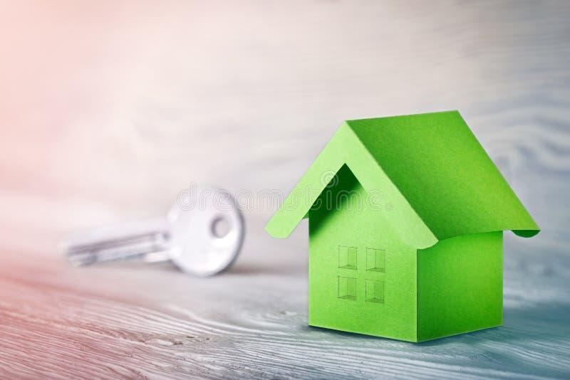 Concetto della proprietà, chiave e casa di carta con le finestre di schizzo su fondo di legno leggero Idea per il concetto del be immagine stock