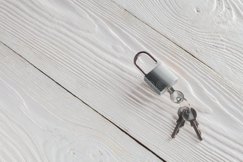 Concetto della proprietà con il simbolo di sicurezza, lucchetto della serratura con la chiave su fondo di legno immagine stock libera da diritti