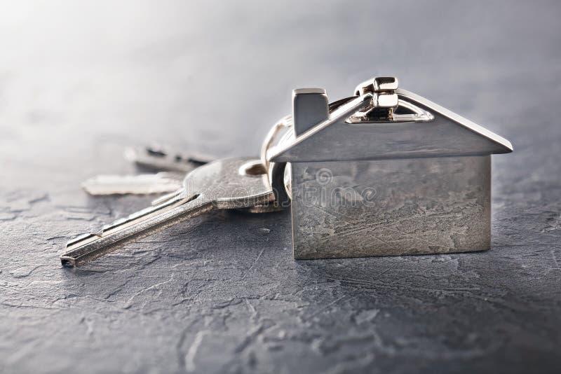 Concetto della proprietà con la chiave, keychain con il simbolo della casa, fondo di pietra immagini stock libere da diritti