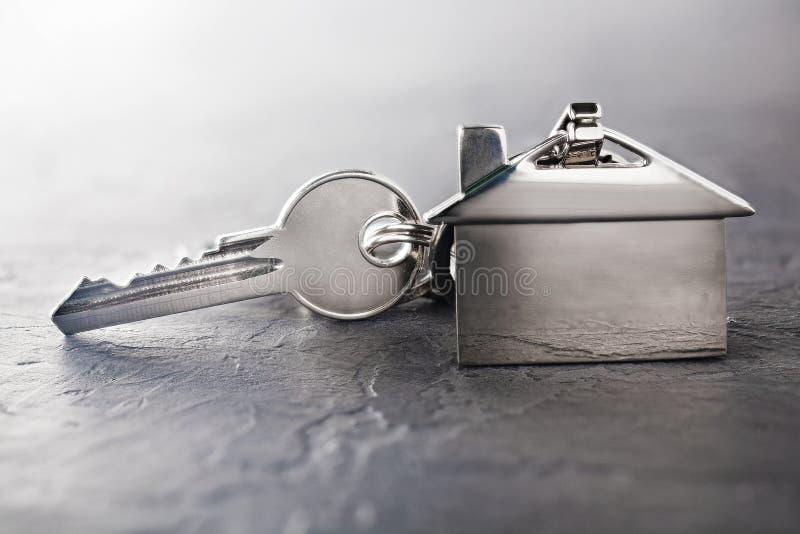 Concetto della proprietà con la chiave, keychain con il simbolo della casa, fondo di pietra immagine stock libera da diritti
