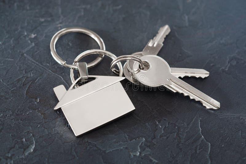 Concetto della proprietà con la chiave, keychain con il simbolo della casa, fondo di pietra fotografie stock libere da diritti