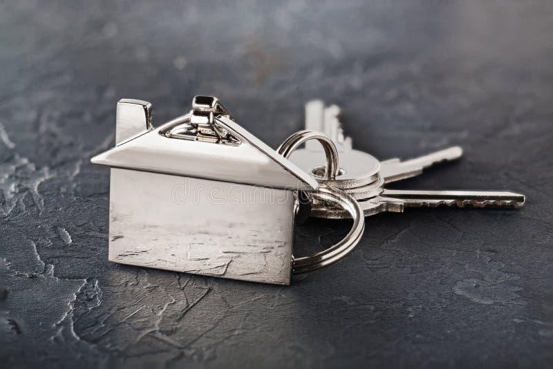 Concetto della proprietà con la chiave, keychain con il simbolo della casa, fondo di pietra fotografia stock