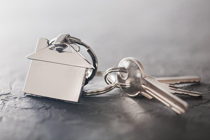 Concetto della proprietà con la chiave, keychain con il simbolo della casa, fondo di pietra fotografia stock libera da diritti