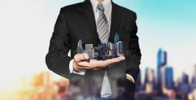 Concetto della proprietà del bene immobile, agente immobiliare di affari che tiene le costruzioni moderne a disposizione fotografia stock libera da diritti