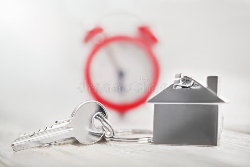 Concetto della proprietà, keychain con il simbolo della casa, orologio rosso, acquisto di tempo fotografia stock