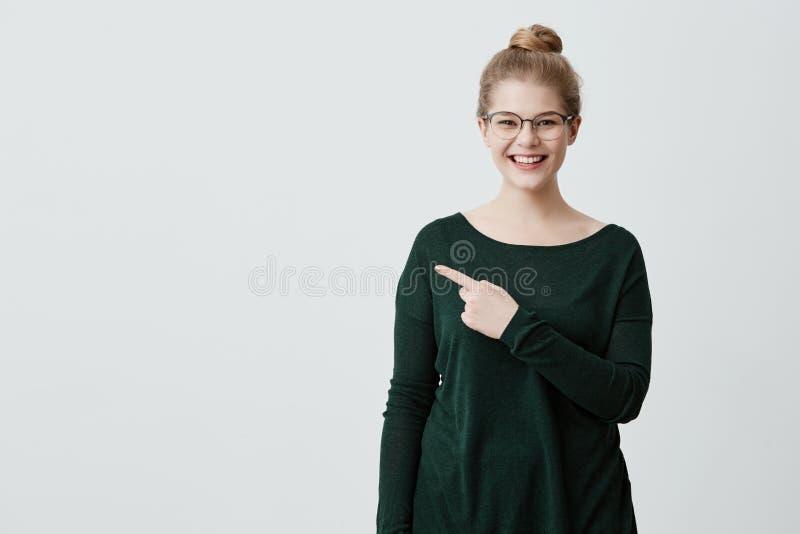 Concetto della pubblicità Giovane signora con capelli biondi, occhiali alla moda in maglione verde ed espressione allegra fotografia stock