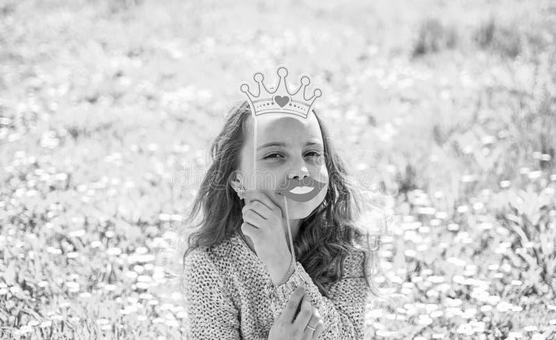 Concetto della regina di umore La ragazza si siede su erba a grassplot, fondo verde La ragazza sul fronte allegro spende lo svago immagini stock libere da diritti