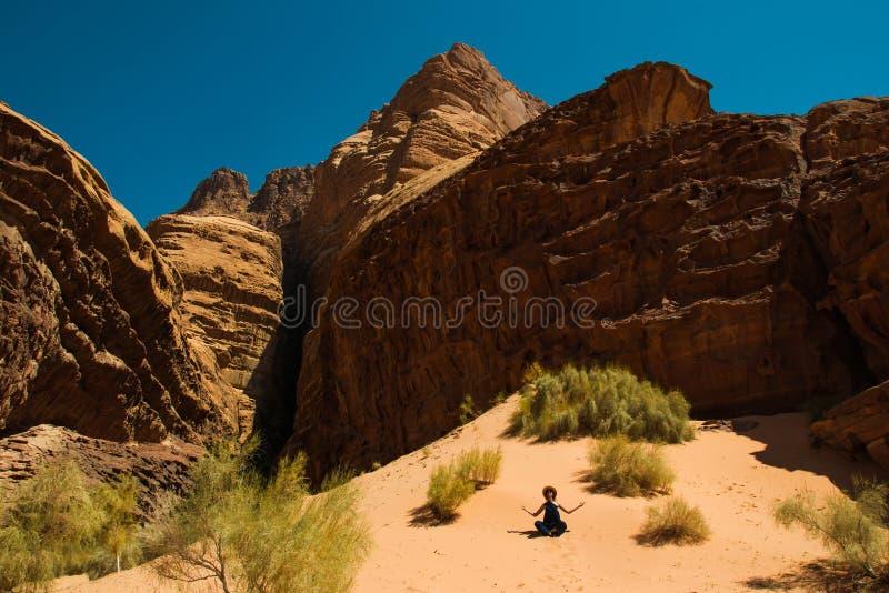 Concetto della ritirata di ispirazione Meditazione di rilassamento della ragazza nel deserto di Wadi Rum, Giordania Stile di vita immagini stock libere da diritti