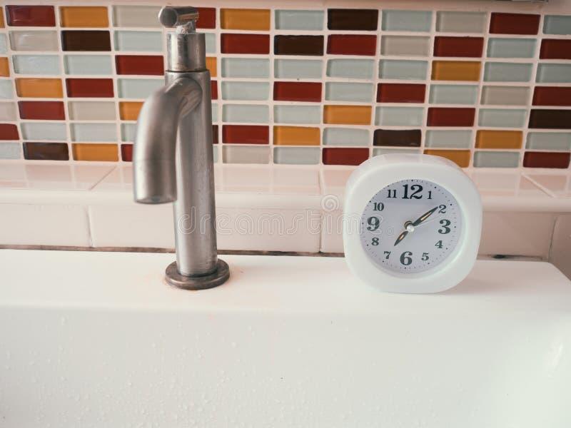 Concetto della routine di vita con l'orologio nel bagno immagine stock libera da diritti