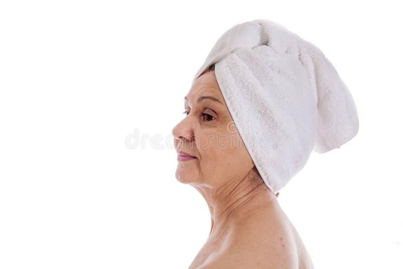 Concetto della stazione termale Bella donna invecchiata con l'asciugamano bianco sulla sua testa fotografie stock libere da diritti
