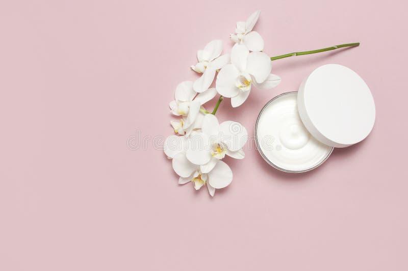 Concetto della stazione termale di bellezza Recipiente di plastica aperto con crema ed i fiori bianchi dell'orchidea di phalaenop immagine stock