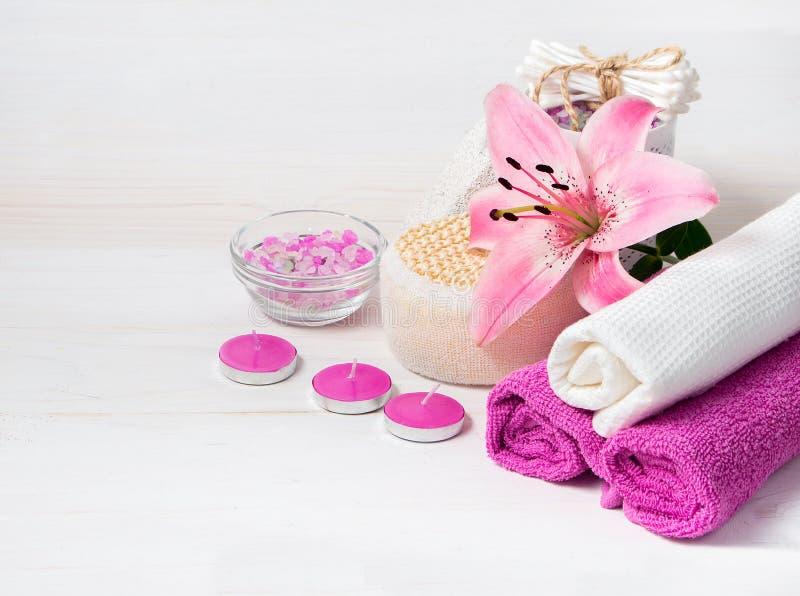 Concetto della stazione termale Fiore rosa del giglio, sale marino, candele, asciugamani immagini stock libere da diritti