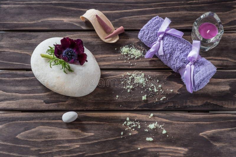 Concetto della stazione termale fiori, candele, sale aromatico e towe di porpora del bagno fotografia stock libera da diritti