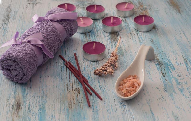 Concetto della stazione termale fiorisca le candele, la porpora aromatica del sale, del sapone e del bagno fotografia stock