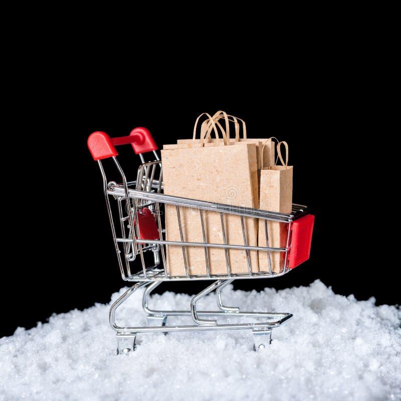 Concetto della vendita di inverno Il carrello con i sacchi di carta in neve è fotografie stock