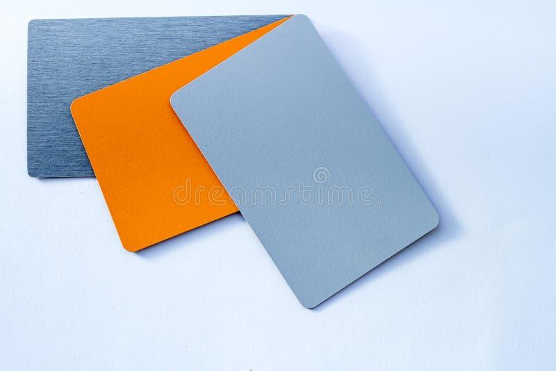 Concetto delle carte di colore sulla gradazione di grigio bianca di colori del fondo tre e dell'isolato arancio su fondo bianco fotografia stock libera da diritti
