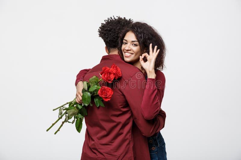 Concetto delle coppie - giovane coppia afroamericana che si huging e che tiene rosa rossa romantica immagini stock