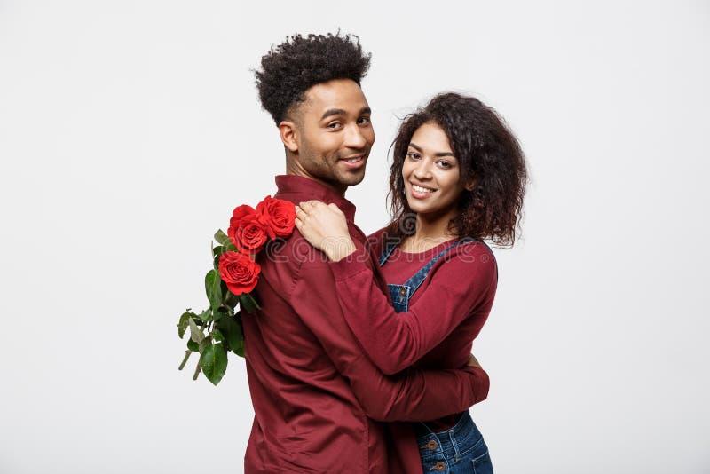 Concetto delle coppie - giovane coppia afroamericana che si huging e che tiene rosa rossa romantica fotografia stock libera da diritti