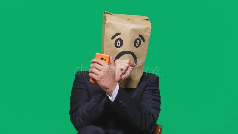 Concetto delle emozioni, gesti un uomo con i sacchi di carta sulla sua testa, con un emoticon dipinto, timore fotografie stock