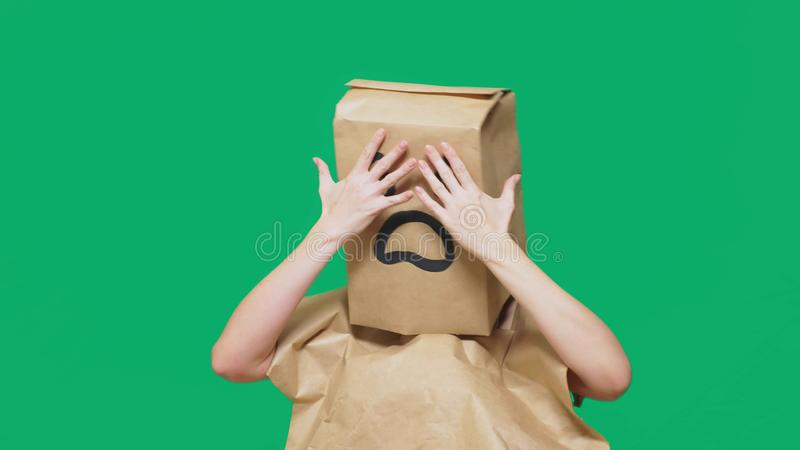 Concetto delle emozioni, gesti un uomo con i sacchi di carta sulla sua testa, con un emoticon dipinto, timore fotografie stock libere da diritti