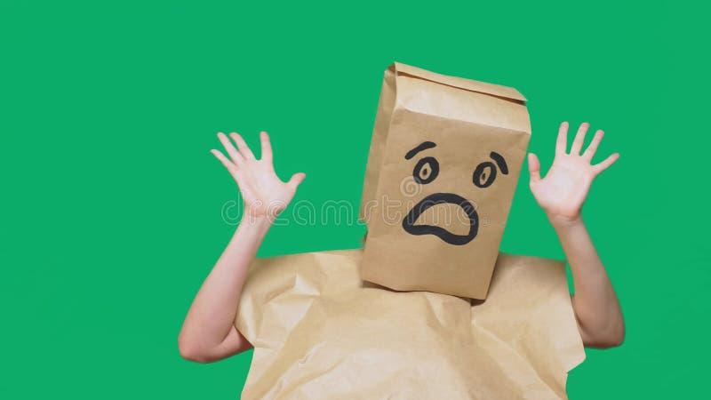 Concetto delle emozioni, gesti un uomo con i sacchi di carta sulla sua testa, con un emoticon dipinto, timore fotografia stock