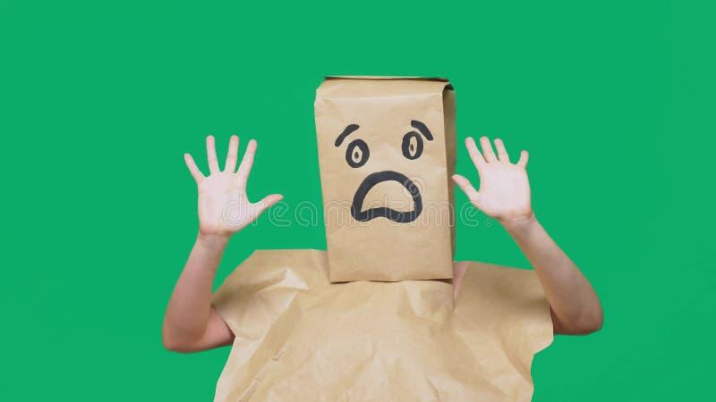 Concetto delle emozioni, gesti un uomo con i sacchi di carta sulla sua testa, con un emoticon dipinto, timore fotografia stock libera da diritti