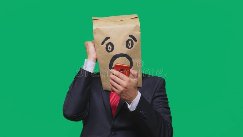 Concetto delle emozioni, gesti un uomo con i sacchi di carta sulla sua testa, con un emoticon dipinto, timore Parlando su un tele immagine stock libera da diritti