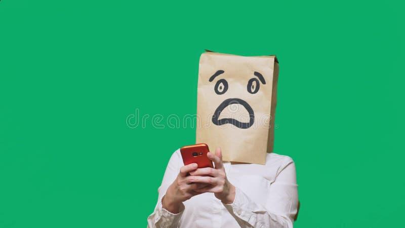 Concetto delle emozioni, gesti un uomo con i sacchi di carta sulla sua testa, con un emoticon dipinto, timore Parlando su un tele fotografie stock libere da diritti
