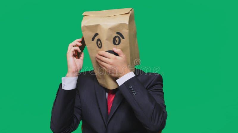Concetto delle emozioni, gesti un uomo con i sacchi di carta sulla sua testa, con un emoticon dipinto, timore Parlando su un tele fotografia stock