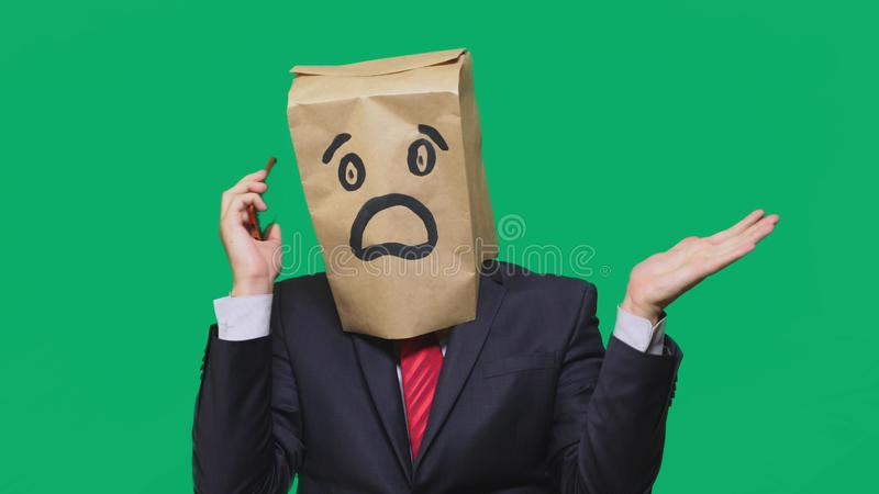 Concetto delle emozioni, gesti un uomo con i sacchi di carta sulla sua testa, con un emoticon dipinto, timore Parlando su un tele fotografia stock libera da diritti