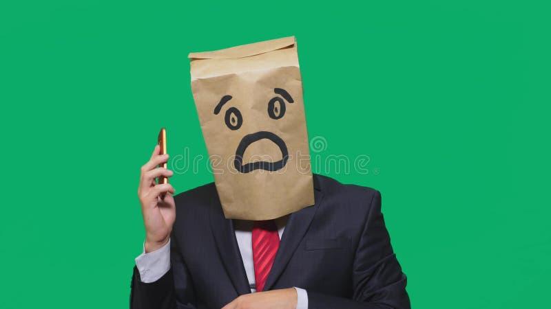 Concetto delle emozioni, gesti un uomo con i sacchi di carta sulla sua testa, con un emoticon dipinto, timore Parlando su un tele immagine stock