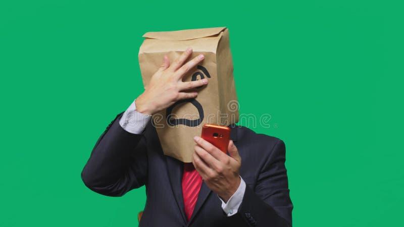 Concetto delle emozioni, gesti un uomo con i sacchi di carta sulla sua testa, con un emoticon dipinto, timore Parlando su un tele immagini stock