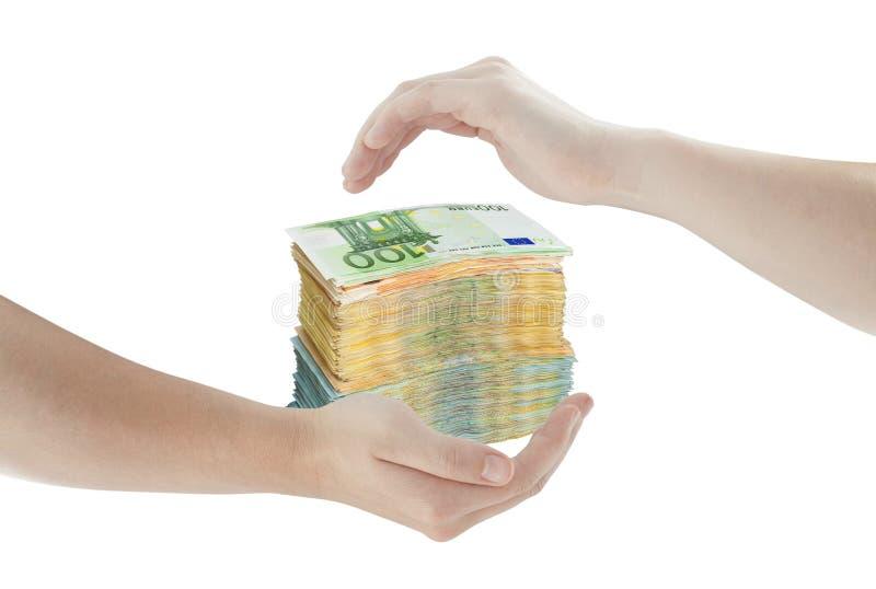 Concetto delle mani che proteggono mucchio di soldi immagine stock