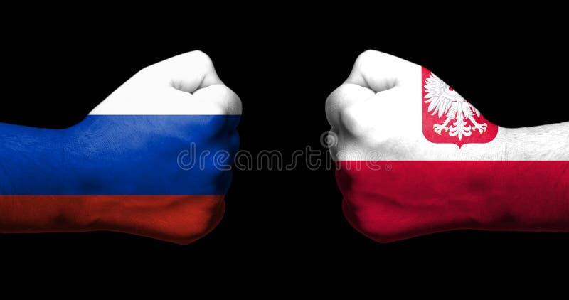 Concetto delle relazioni/conflitto fra la Polonia e la Russia simbolizzato da due pugni chiusi opposti a immagine stock