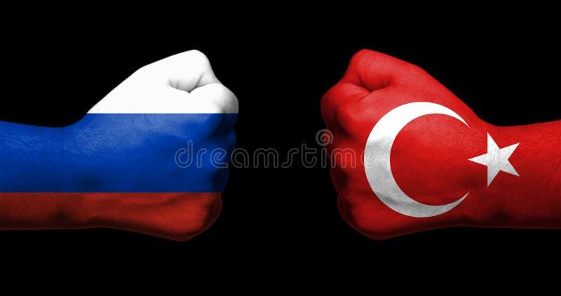 Concetto delle relazioni fra la Russia e Turchia simbolizzate da due pugni chiusi opposti a immagini stock libere da diritti