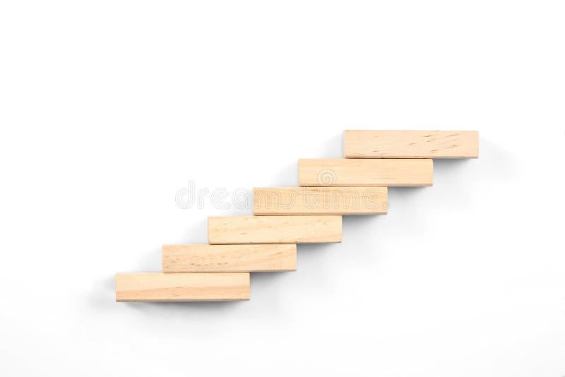 Concetto delle scale; i blocchetti di legno del giocattolo fanno le scale isolate su fondo bianco con lo spazio della copia per i fotografia stock libera da diritti