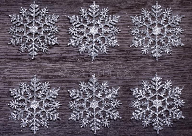 Concetto delle vacanze invernali, sfondo di sei fiocchi di neve su una superficie di legno fotografia stock libera da diritti