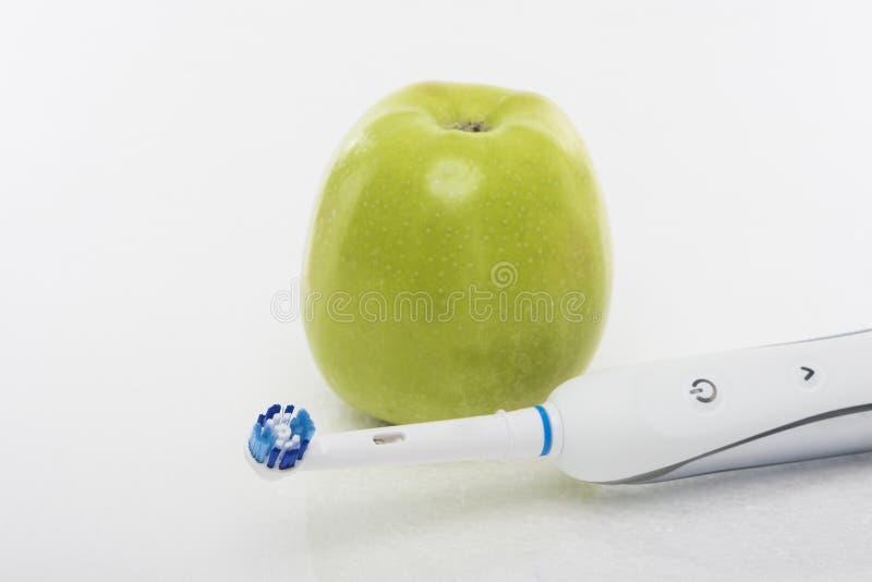 Concetto dentario di Hygien: Mela verde insieme a Toothb elettrico fotografia stock
